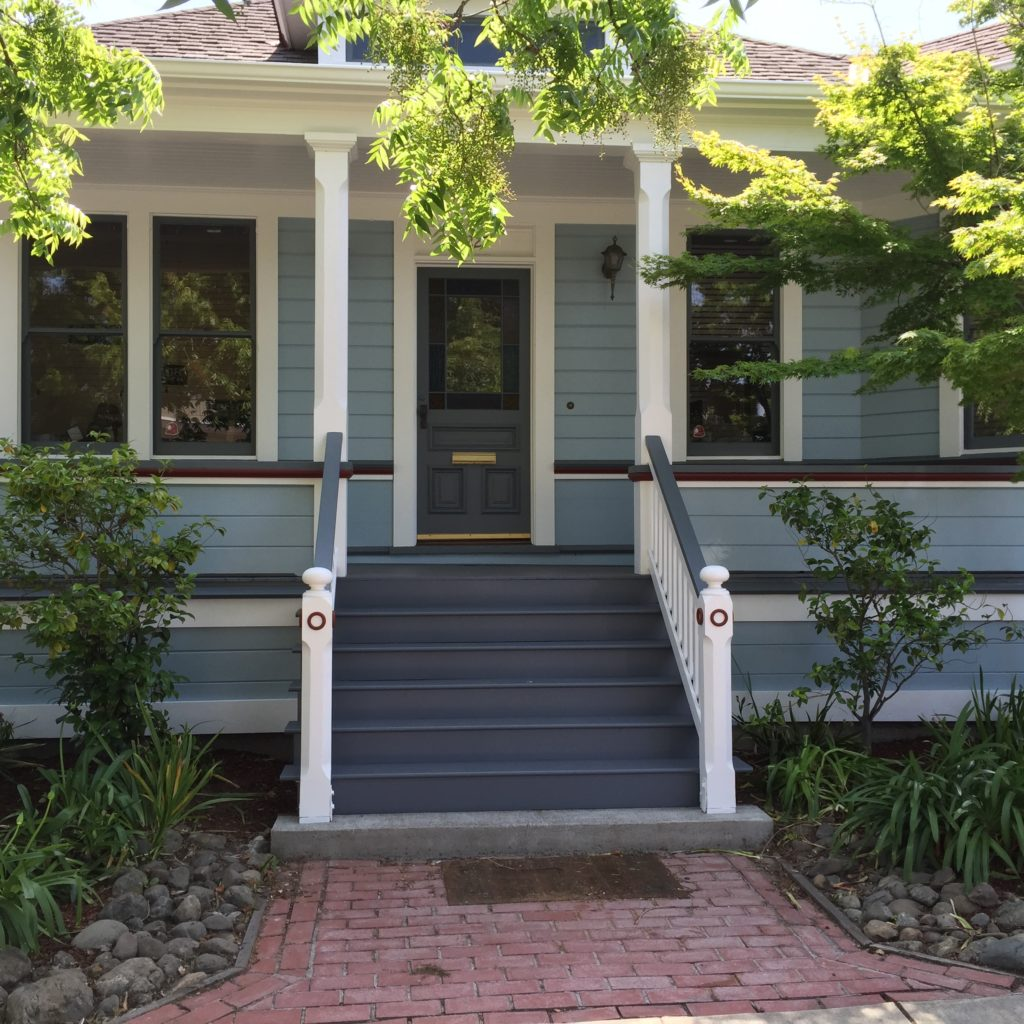 view of front of one story blue house with brick walkway and navy stairs going up to porch