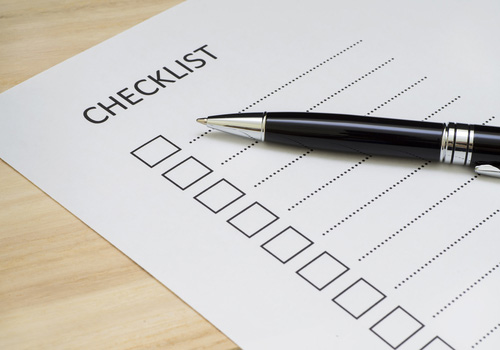 blank checklist sheet with black pen resting on it