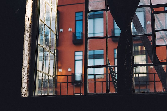 view looking out of window at red apartment building with tall windows.