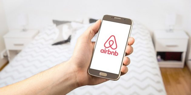 Photo: Person holding a phone displaying AirBNB logo