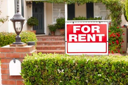 view of front of house from sidewalk looking over hedge at red and white for rent sign