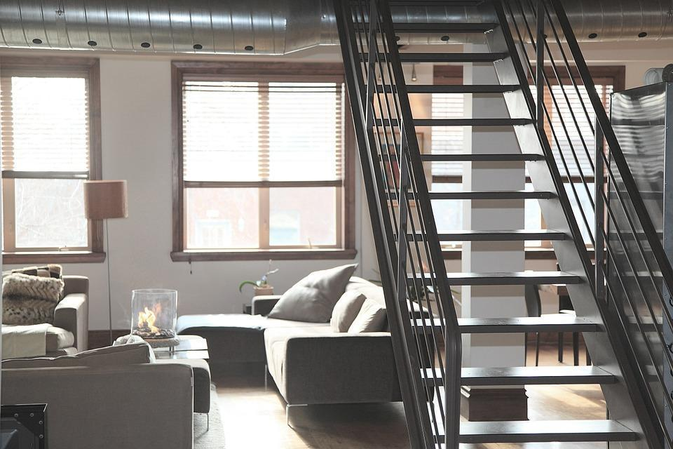 apartment living room with grey sectional furniture and a black metal staircase