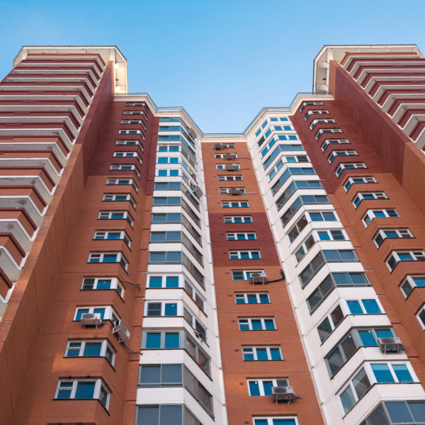 street view looking upward at red brick apartment building