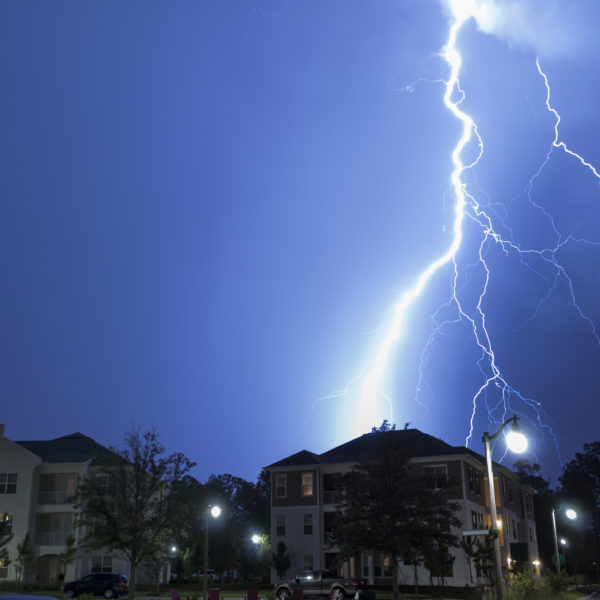 large bolt of lightning striking the earth behind an apartment complex at night