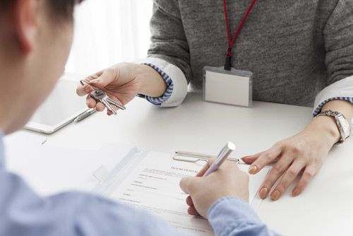 man signing a document and woman handing over keys