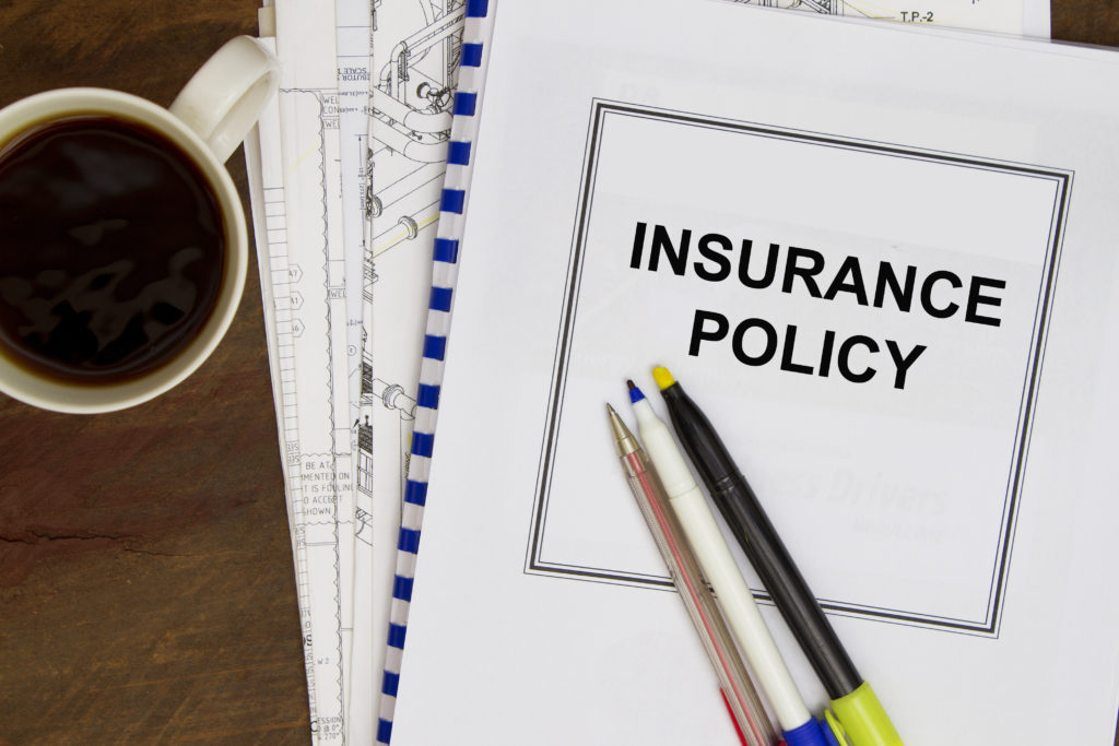 Insurance policy paperwork with pens and cup of black coffee next to them