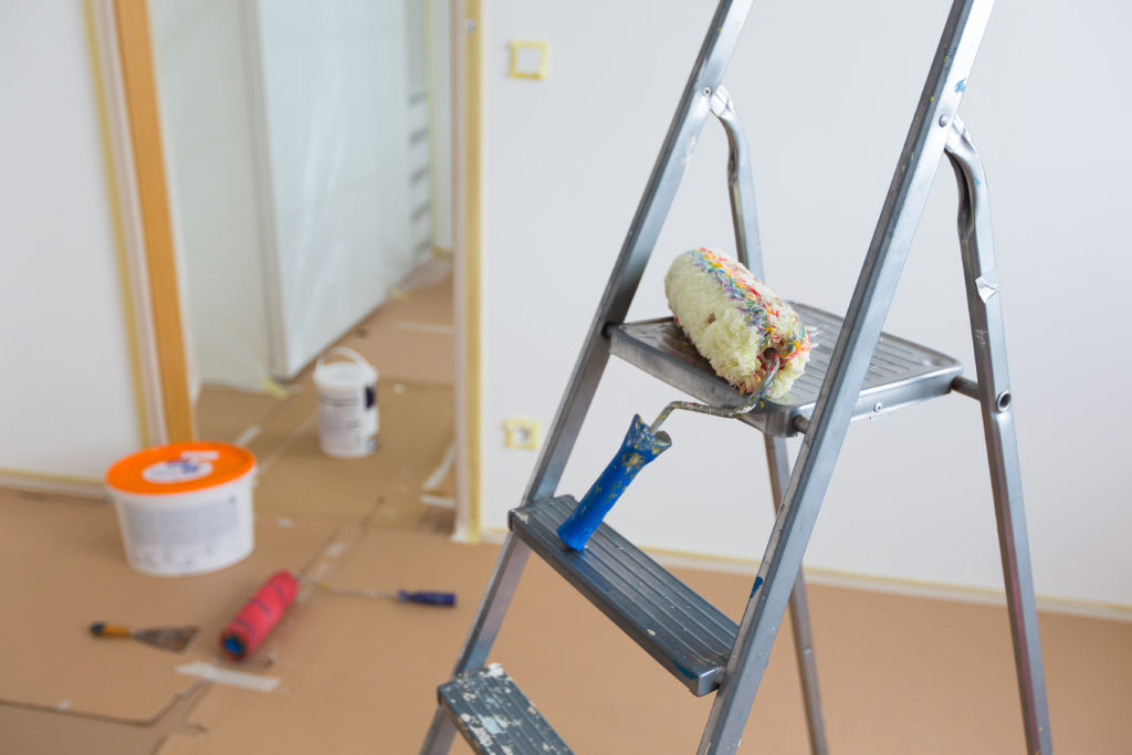 metal painters ladder inside of room being prepped for painting