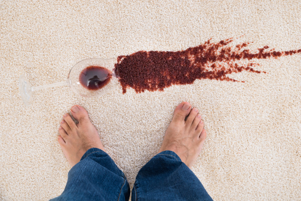 man's point of view looking down on beige floor where glass of red wine is spilled