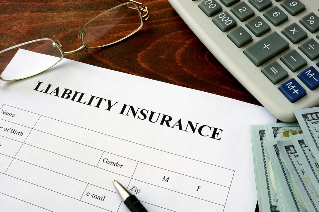 liability insurance form with gold glasses, pen, calculator and money