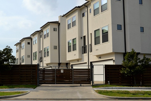 street view of tan, three-story condo building behind a brown gated fence