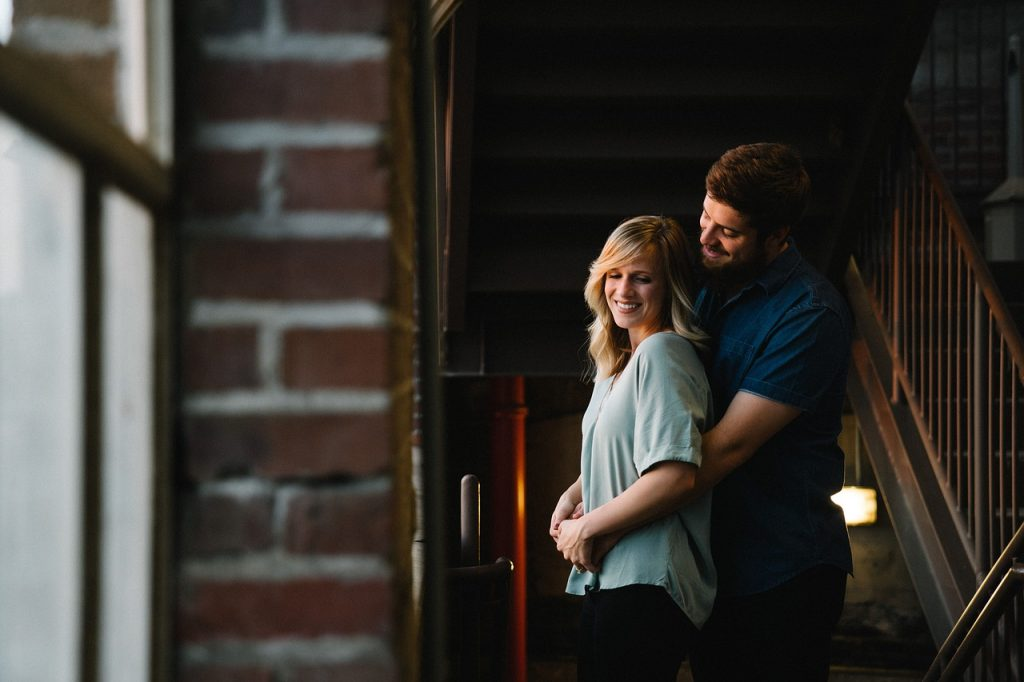 man hugging woman from behind while standing in an old stairwell