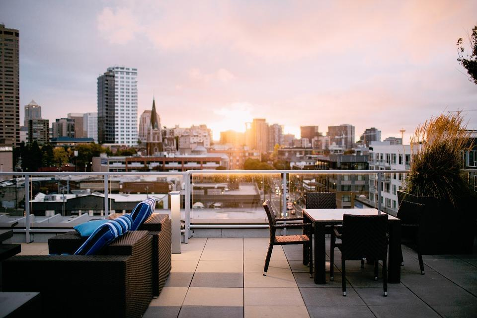 view of city from top of a building patio during sunset